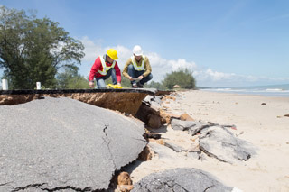 men working on road eroding onto beach